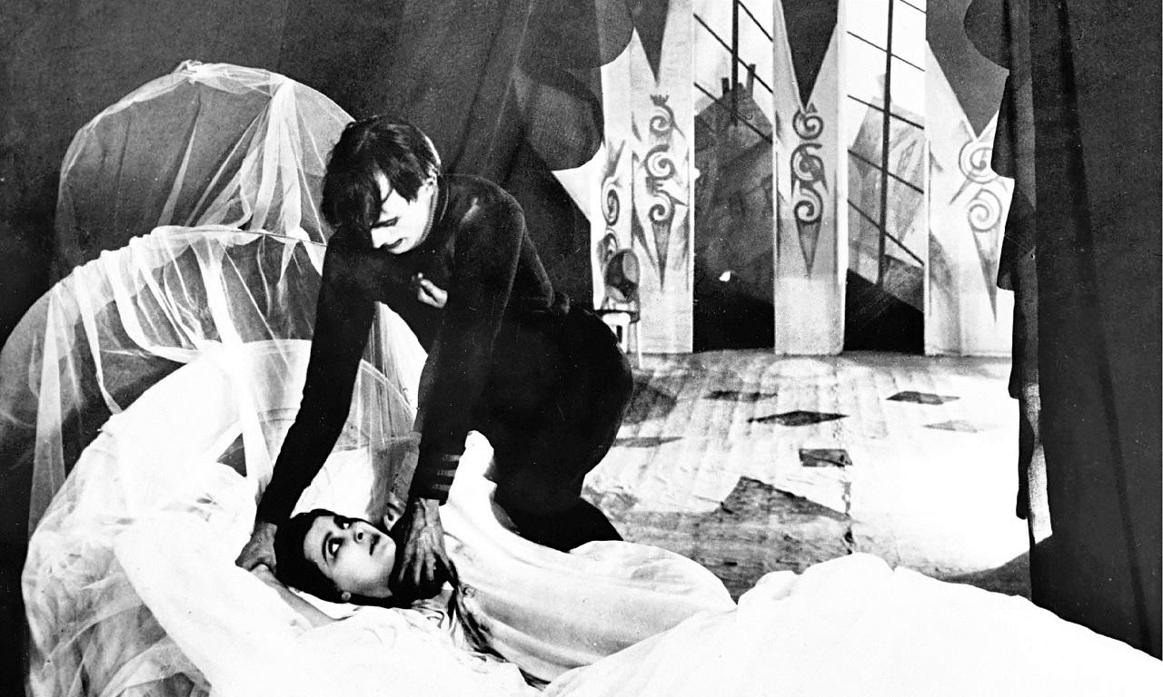 Сомнамбула и красавица на фоне причудливой архитектуры – кадр из фильма-основоположника экспрессионизма «Кабинет доктора Калигари»